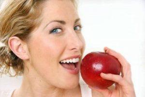 Blonde woman eating apple
