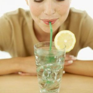 Close up of woman drinking lemonade with a straw