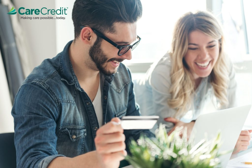 Man and woman smile while looking at a laptop, man is holding a credit card, CareCredit logo in top left corner
