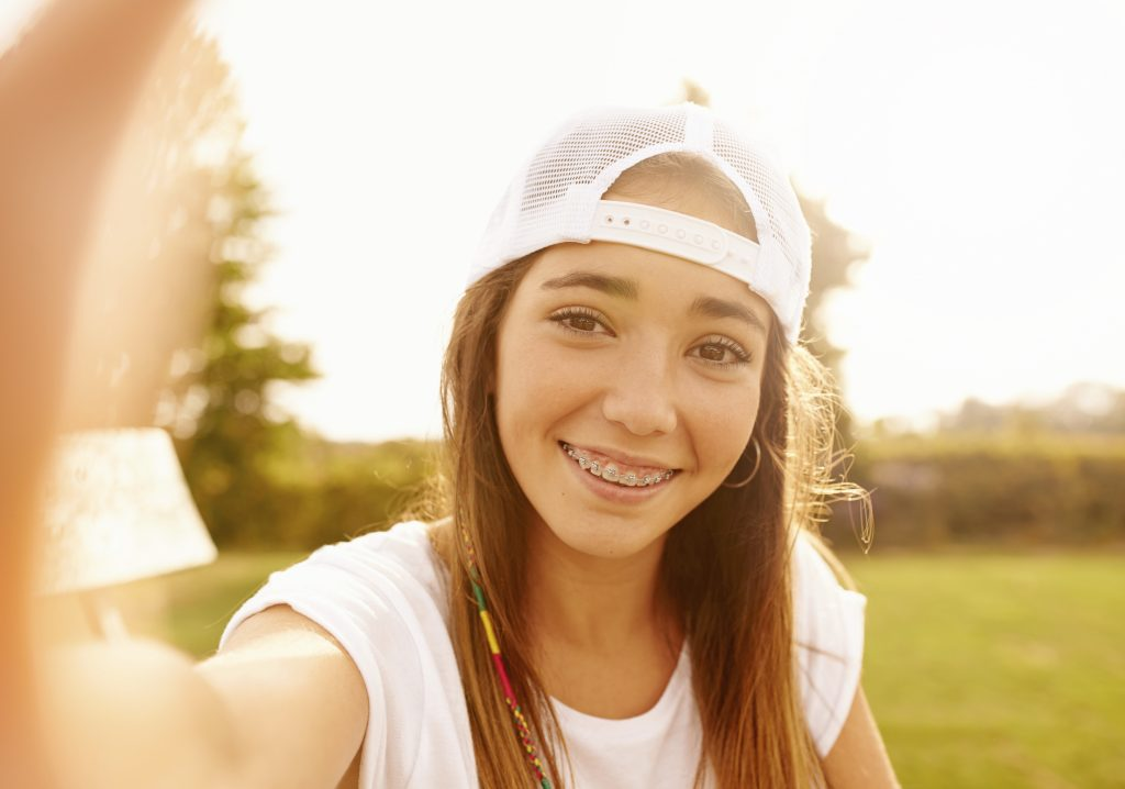 Girl with braces takes selfie in a field