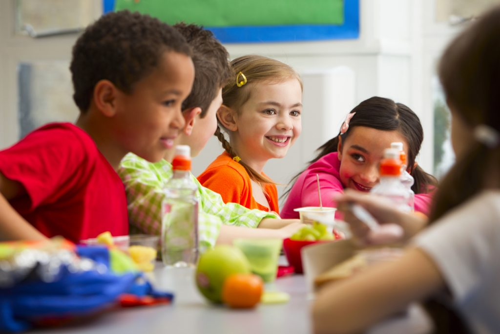 Group of children having packed lunches