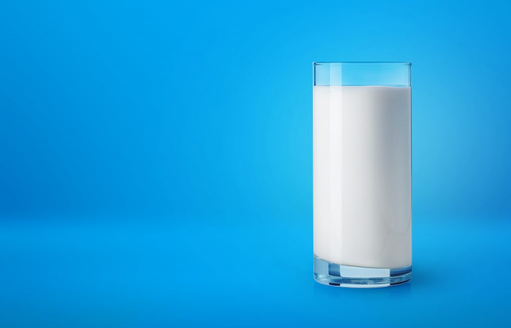 Glass of fresh milk on blue background